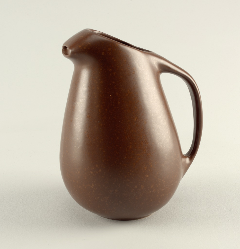 Brown pitcher of teardrop-like body with curved handle, open mouth, and angular spout.