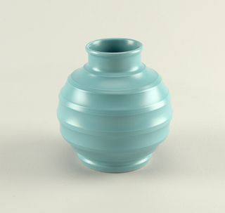 Globular form with circular mouth, short neck, circular foot; horizontal ridges throughout body; blue-green matte glaze.