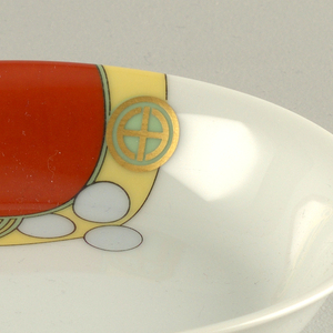 """Circular dish with curved sides and slightly flaired lip; decorated with abstract enamel decal with pattern of interlocking circles in red, pale blue, yellow and green, all outlined in black. Gilded """"mon"""" insignia over circle decoration at one side."""