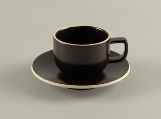 Round form cup with straight top and sides and a D-shaped handle.  Plate is a round form. Both are decorated in a matte black finish.  The rim of both the cup and the plate is decorated in a matte creamy stone color.
