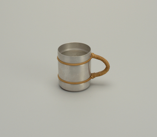 Round aluminum mug with rattan bands at top and bottom, and semi-circular rattan-wrapped handle.