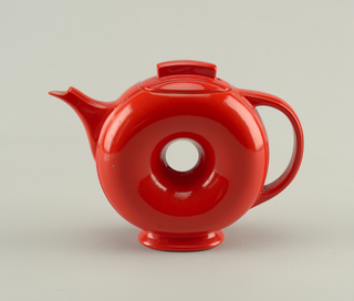 Teapot (a) of upright donut-shape with spout on one side, D-shaped handle on the other, and flairing circular foot. Lid (b) with long tab handle at top center.