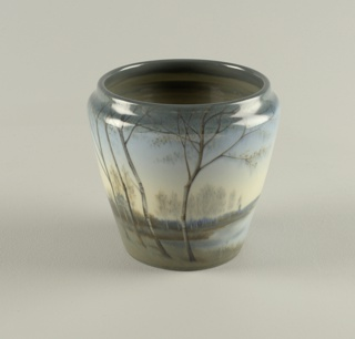 White clay body, cast.  Wide flaring cylindrical body with truncated rim; no foot.  Underglaze slip-decorated around body with landscape scene of lake, low hills and trees in background.  On front is a cluster of birch trees in foreground.  Colors range from blues to grays, with accents of browns in the trees.  Allover clear high glaze; fine crazing.  Interior and bottom glazed.