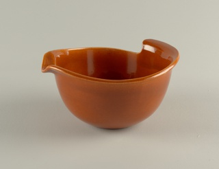 Rust glazed deep circular bowl with wide rim, the irregular edge turned out to form a spout and hand grip.