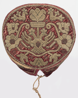 Cap with metallic embroidery on red velvet with a symmetrical plant motif, confronted birds and a double-headed eagle in the center of the crown. Simple floral vine pattern on the brim. Brim very broad in the front and narrow in the back. Inside lined with printed linen, possibly from the first half of the eighteenth century, in a brown and blue floral pattern on a red ground.