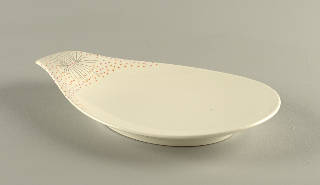 Teardrop form platter with extended handle that bears decoration of painted floral pattern: black lines with pink and orange dots.