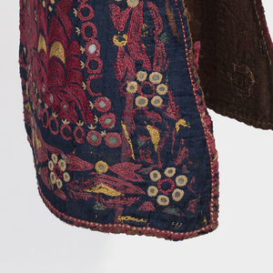 Round pointed hat with a shoulder cape. Dark blue silk with all-over closely-spaced formalized flower design in red, yellow, green and cream silks and round bits of mirror glass. Backed with heavy red cotton.