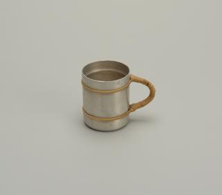 Round aluminum mug with rattan bands at top and bottom, and semi-circular rattan-wrapped handle.