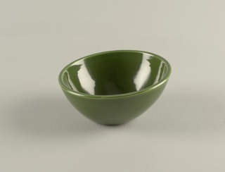 Green glazed deep circular bowl rising to a wide canted mouth.