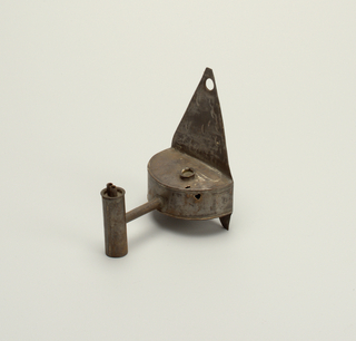 One of a pair of whale oil lamps. Flat semicircular container with brass cup over the filling hole; attached to a triangular piece of tin, arched below and with hole at top; at the front of the container a pipe connecting with upright cylinder which is fitted with two brass tubes and a brass plate. -a and -b are the same.