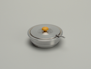Circular, wide-rimmed dish (a) decorated with horizontal striations on exterior; contains removable pierced circular strainer (c); circular lid (b) with yellow Bakelite knop and notched at edge to accept long-handled three-pronged fork (d).