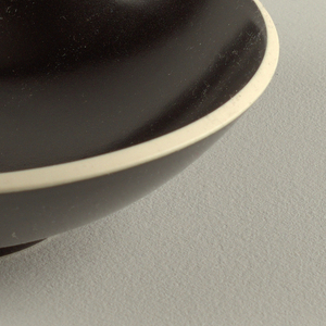 Rounded tapering form decorated in a matte black finish.  Rim decorated in a matte creamy stone color.