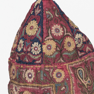 Cap made of triangular sections coming to a point at the top and finished with a tassel; forehead band and square at back falling to shoulder.  Dark red satin with embroidery (principally chain stitch) in design of open flowers with leaves and birds.  Lined with tan linen.