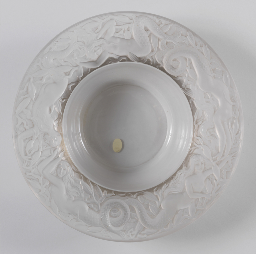 Clear glass bowl with pronounced lip that projects out from bowl ( approx. 2 inches) ;Lip is frosted glass decoracted with mermaids in high relief.
