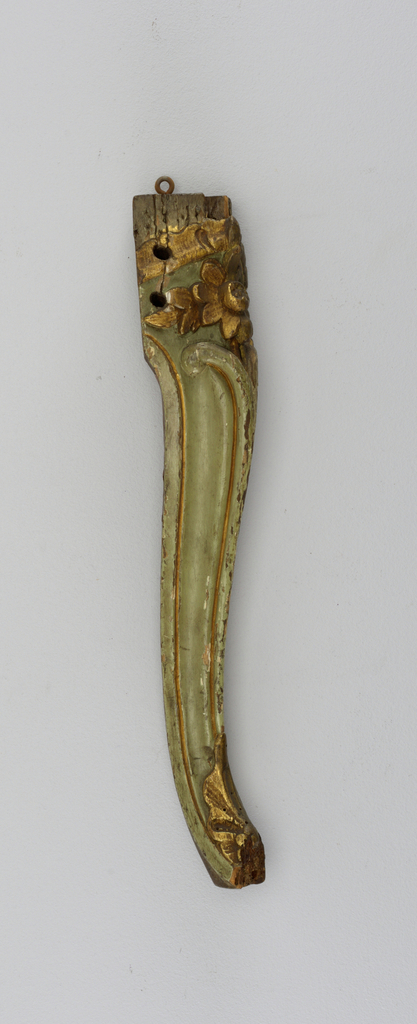 Front leg of a chair, left side; cabriole, leaf foot, gilded, and gilded flower and tattered frill above knee.