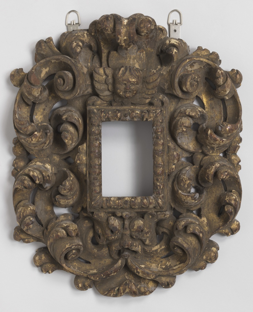Oval. Centered with vertical rectangular opening with cherub's head above and grotesque mask below. Edged with scrolling leaves. Boldly carved and pierced.