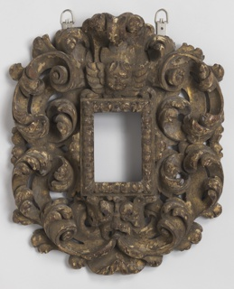 Carved foliate C-scrolls surrounding a rectangular opening surmounted by a putto head.