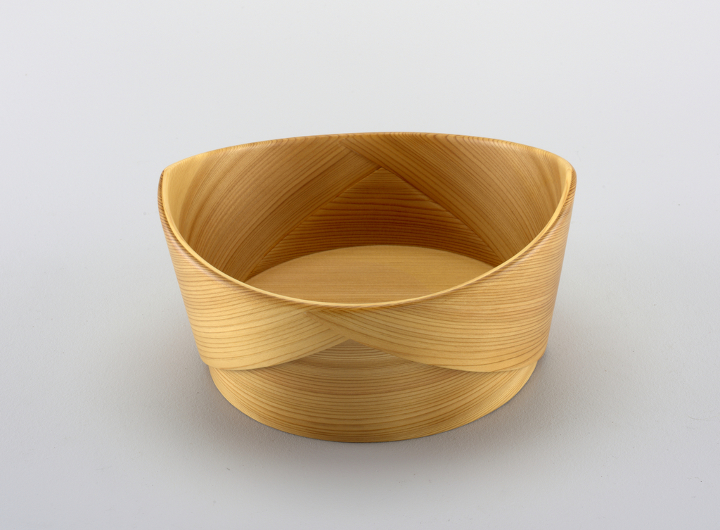 Bowl constructed single pale, unstained cedar strip, wrapped around flat bottom to create bowl with continuous edge, rising one side. Overlap of strip visible only on outside of bowl.