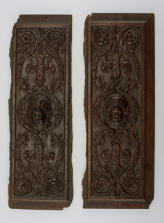 Two doors. In center of each, a woman's head in high relief. Above and below, in reverse position, arabesques of foliage in the shape of a lyre, prolonged at four corners of door to enclose four fleurons of diversified design.