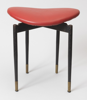 Curved, ovoid seat upholstered in red vinyl on four-legged black enameled metal base; tubular brass sabots on feet.