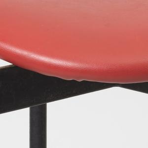 Curved, ovoid seat upholstered in red vinyl on four-legged black enameled metal base; tubular brass sabots on feet.