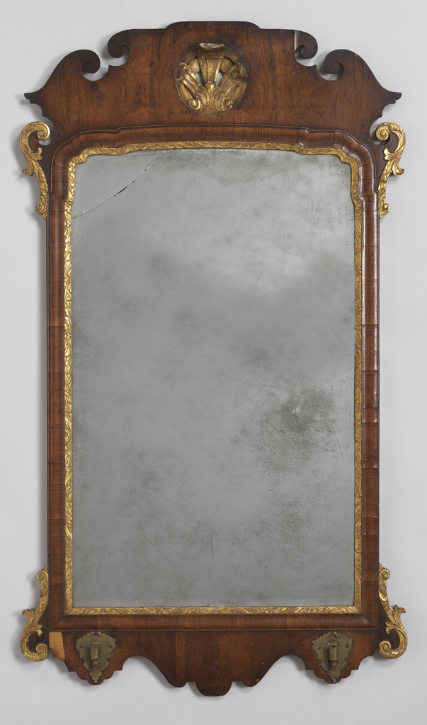 Rectangular mirror (a) with original rectangular bevelled glass. Inner gilt molding carved with regularized floriation in low relief; shaped at upper corners. Wider conforming cyma and bead walnut molding outside. Cresting, with gilded ears of voluted leaf carving, is itself scrolled, voluted, and pierced at center to admit a round pierced gilded ornament. Shaped base has ears similar to above and bears a pair of engraved brass sockets which receive two scrolled candle brackets (b,c) with circular candle sockets and cups.