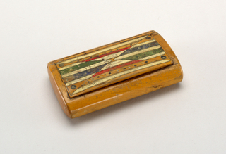Small box, rectangular in plan, oval in section.  Hinged lid, thinly veneered lining of shell. Painted geometric design on top, black lines with green, blue, red, and white filled areas.