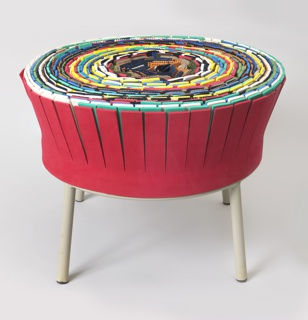 Large multi-colored circular seat composed of found materials--upright sheets of variously colored felt, carpet remnants, foam, plastic--arranged in concentric circles, with regularly spaced slits at tops; gray, tubular metal base with four legs.