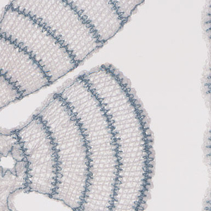 Bioimplantable device for reconstructive shoulder surgery with three tabs of different lengths projecting off a narrow band, machine embroidered in white and blue polyester with the base cloth dissolved for a lace-like effect.