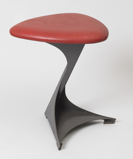 Triangular seat with curved corners, upholstered in red leather, mounted on enameled sheet steel base composed of angled post on trangular foot.
