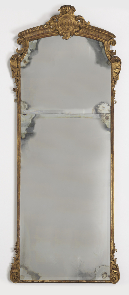 "In early 18th century style, modern bevelled clouded glass in two parts; the upper part shaped to conform to the narrow inner molding which runs within the entire frame. Lower corners bear leaf carvings terminating in volutes and scrolls. Similar elements are reversed at upper corner and are contiued into the cresting by smaller voluted leaf carvings. The gadrooned and leaf carved cavetto-molded cresting is interrupted at its center by a foliated cartouche bearing in relief on its circular cabachon the cipher ""10"" repeated and reversed."
