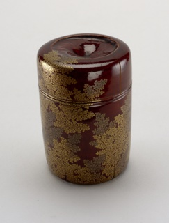 Cylindrical box with cover, made of a segment of a bamboo stem. Ferns in gold 'hira-makiye' lacquer on ground of 'shunkei-nuri' (reddish-brown) lacquer. The depressions in top and underneath are due to formation of the node of the bamboo segment. The ferm is a symbol associated with Japanese New Year's ceremonies.