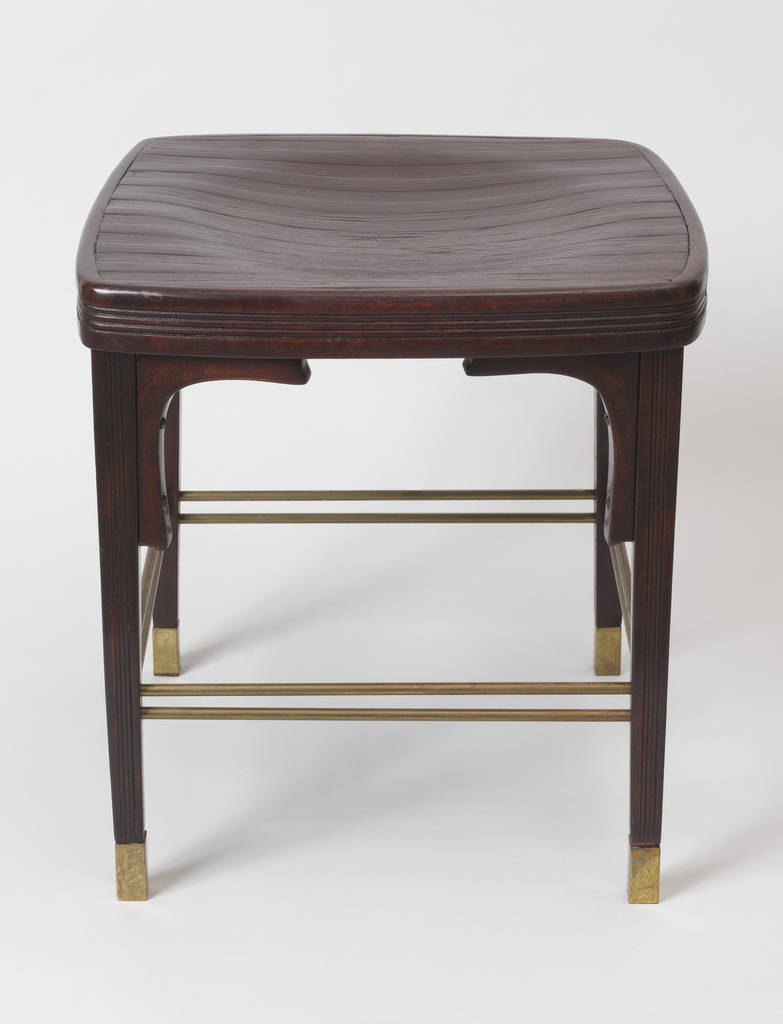 Dark brown form consisting of square seat with rounded corners and circular indentation in top, on four tapering legs with arc-shaped supports below seat, pairs of tubular brass stretchers near feet; brass sabots on feet.