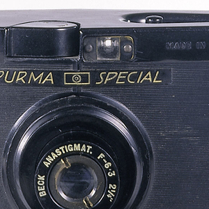 Black, striated Bakelite body of rectangular form, projecting to sharp vertical edge in center front; circular lens in center; small rectangular viewfinder above lens; smooth black top with film-winding wheel on left; two small circular windows with green plastic on center back.