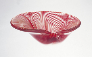 Smooth, heavy glass body in form of half clam shell with rim extended horizontally on one side; thin, swirling latticino stripes of opaque red encased in translucent white, fanning out from glass glob corresponding to hinge of shell.