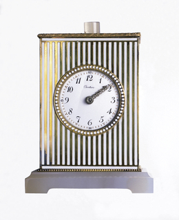 A gold and white striped rectangular clock with a circle face in the middle. The base has a wider foot and small knob on the top. Around the face there is a row of white dots.