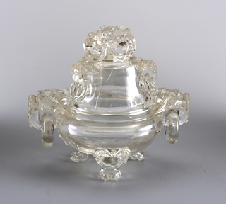 Circular incense burner with circular domed cover; cover surmounted by open-work carving of coiled dragon and lotus; on cover sides are three loose rings suspended from animal mask handles. Body rests on three animal legs extending from lion-dog masks. Pair of handles made up of loose rings suspended from animal masks; transluscent inclusions, both pieces.