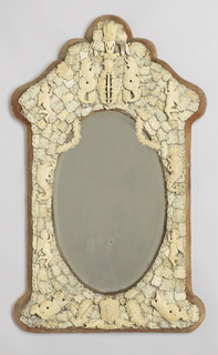 Shield-shaped frame mounted with overlapping plaques of ivory, the arched top with heraldic devices, the bottom overset with fish and a shield, all surrounding an  oval mirror.