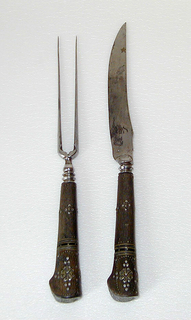 Long two-tined fork, decorated at the inside of the rounded shoulders; short baluster stem. Tapered wooden handle of oval section with beaked end; handle divided latually by bands of laminated horn, silver, gold; handle piqué and inlaid with rozettes and dots of different metals. Rozette on flat end.