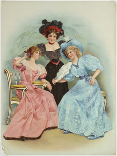 Vertical rectangle. Three young women in front of a potted palm. One at right holds white ostrich fan. Embossed.