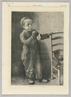 A boy stands with his left hand on the back of a chair and holds up a bubble pipe with his left as he blows bubbles.