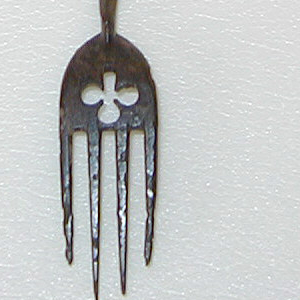 Four-tined fork, sloping shoulders. Neck pierced with trefoil. Scroll stem at neck, paired knops on cylindrical stem. Finial flat openwork scrolls surrounding movable openwork knop with loose bead inside.