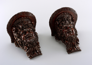 Wall brackets with head of Bacchus. Bearded laughing mask among scrolls and vintage motifs supports a shaped shelf moulded with a bound laurel fillet.