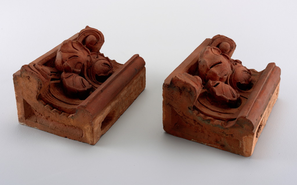 Horizontal, concave corice pieces with vegetal forms in relief.
