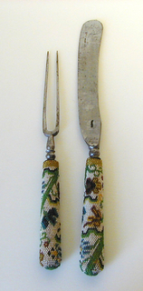 Scimitar-shaped blade. Tapered handle decorated with multi-colored glass beads; floral pattern in green, blue, brown and yellow on white ground.