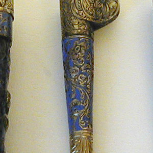 Small blade straight-sided, the upper edge tapering towards the point. Blue enameled handle has silver mounts decorated with floral pattern. Handle flaring with a projecting ear on one side.