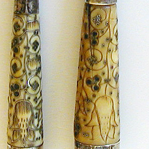 Sabre-shaped blade, rounded bolster, plain silver ferrule. Tapered ivory handle, stained red and green and inlaid with floral designs in silverwire. Plain silver cap with rounded top.