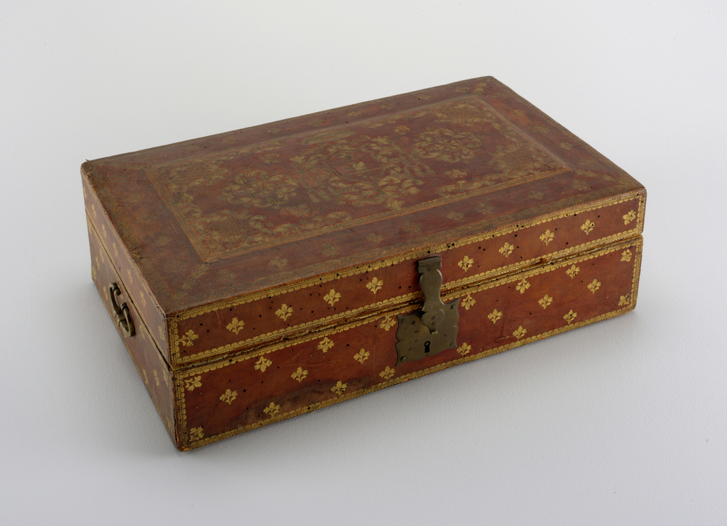 rectangular wooden box, on oiutside covered with gold-tooled leather; sprigs of flowers on sides and surrounding raised central panel of cover, which in center bears coat-of-arms flanked by two quatrefoils, and in corners diapered scrolled cartouches - coat-of-arms: tierced in fess, 1] an eagle displayed, 2] a winged dragon, 3] three mullets on bend - surmouted by cardinal's hat - brass escutcheon, hasp, and two bail handles - inside lined with red undrressed leather.