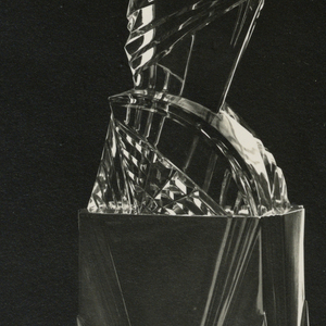 Photograph of a glass vase with fluted areas and a cube-like base.