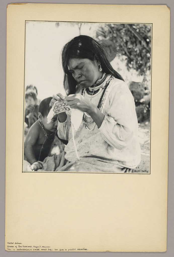 Woman embroidering a small bag. [SEE CURATORIAL REMARKS]